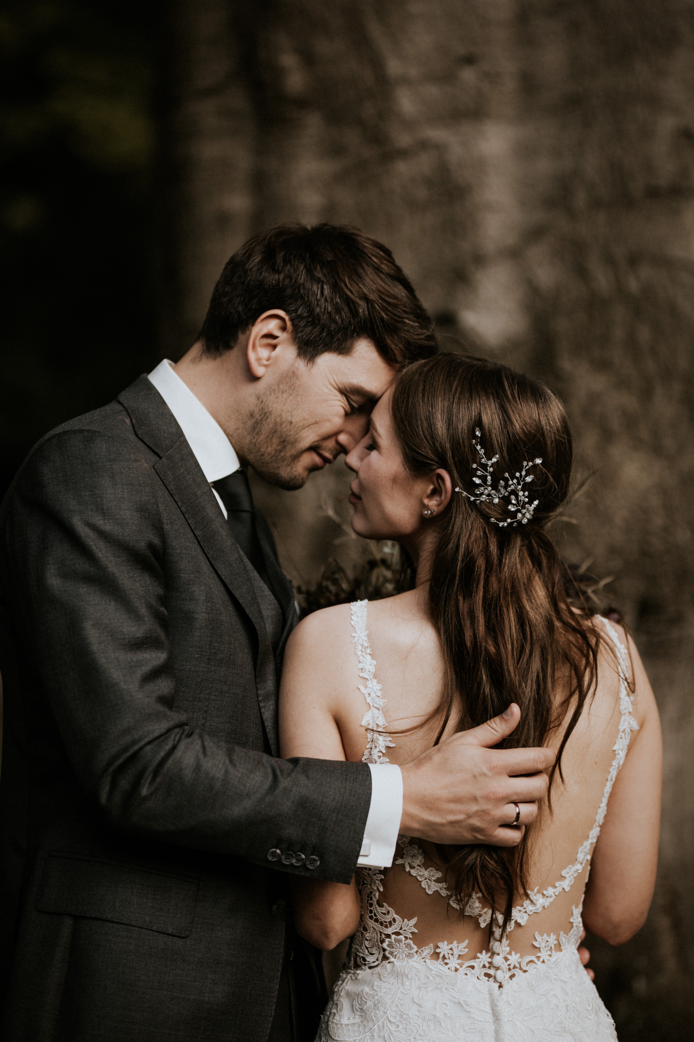 Groom and bride with beautiful hair piece cuddling in the Scottish woods