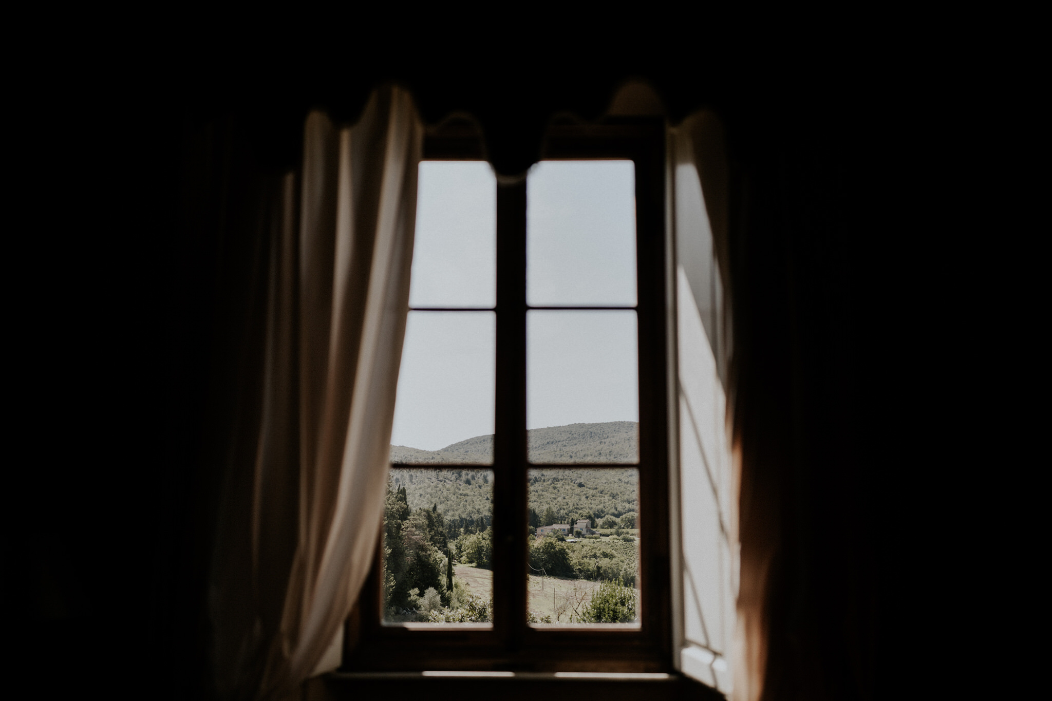 View of sunny fields and trees through a window in the Val d'Orcia, Borgo Stomenanno, Italy